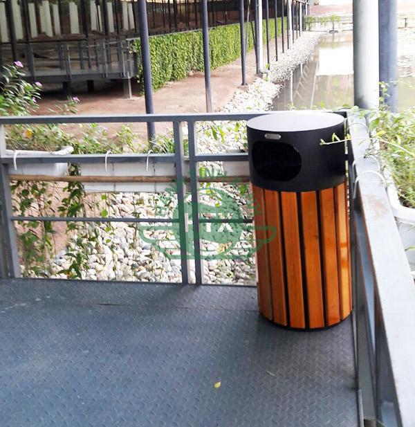 Thùng rác gỗ tròn với cửa xả rác ở mặt trước